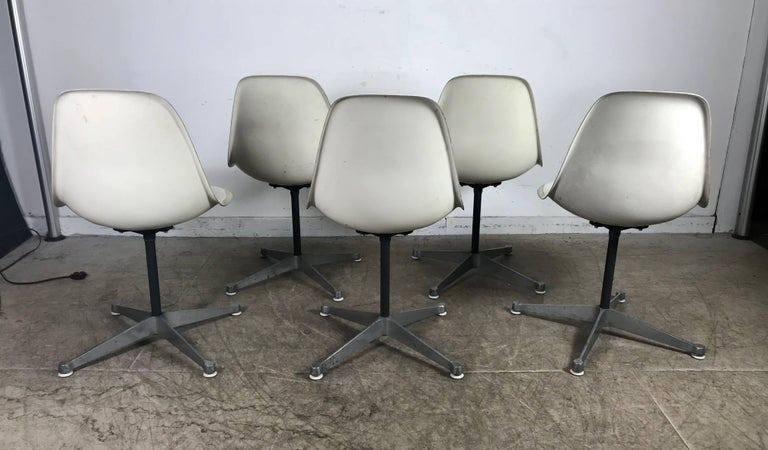 Six Classic Mid-Century Modern fiberglass swivel side shell chairs designed by Charles and Ray Eames, manufactured by Herman Miller. Remarkable condition for there age, early example, beautiful white fiberglass side shells atop cast aluminum four