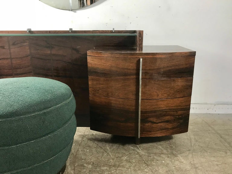 Stunning and quite rare Gilbert Rohde Art Deco rosewood dressing table, pouf and mirror, purchased recently from an amazing estate, folks originally purchased new from Herman Miller showroom in 1937..Vanity features bookmatched rosewood, with four