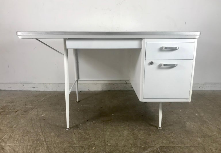Modernist lacquered steel desk. Metal industrial. All steel industrial desk with faux wood laminate top. Fully restored and professionally lacquered in a beautiful white. Elegant and functional, featuring generous top pencil drawer, one right drawer