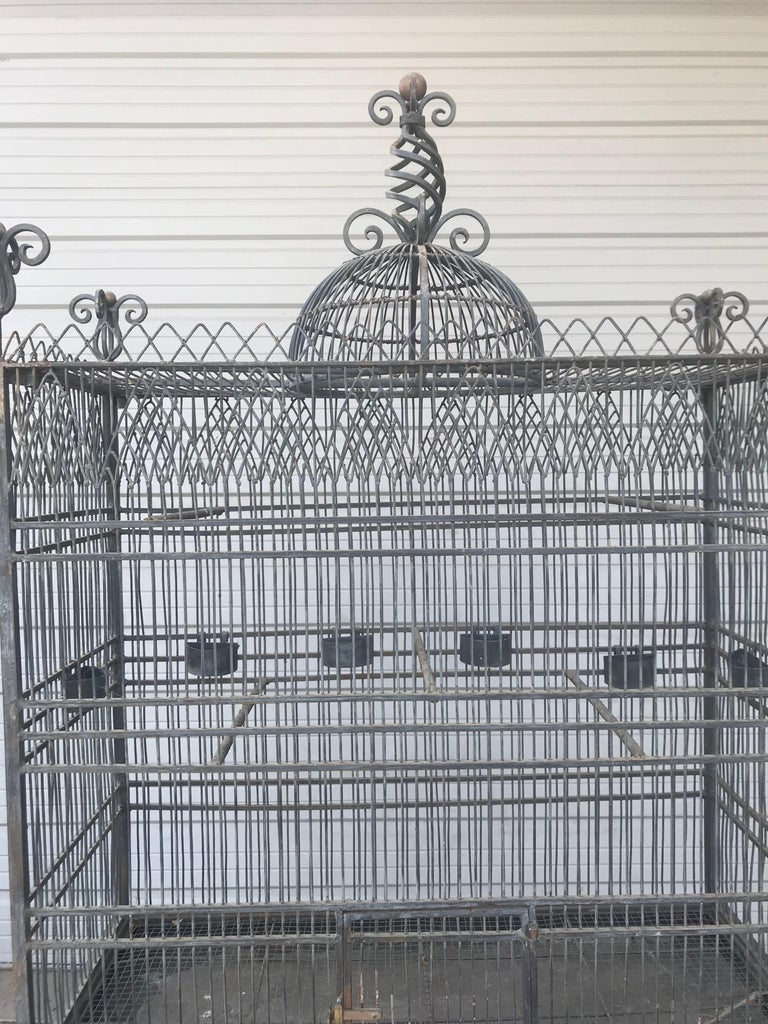 Monumental Victorian style antique brass, painted bird iron bird cage, having a stand that is 33 inches in height this palatial birdcage is constructed of ebony painted iron finish and brass. And is certain to add conversation as well as a fine home