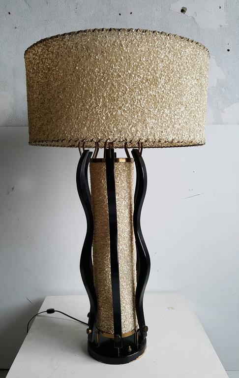 Unusual and rare modern Majestic table lamp..Wonderful curved sculpted wood body,brass detailing and original pebbled parchment shades,,Two light options,,center and top can be luminated seperatly..Top shade measures 22