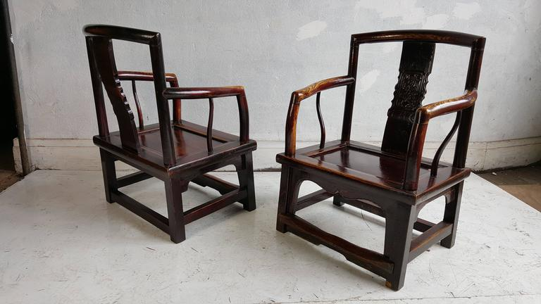 A finely crafted set, four Chinese official's chairs. The center yoke back panel has elegantly carved section. The front leg apron is also beautifully carved. Retains foot rail joining legs. The lacquer finish on the chairs is original. Often this