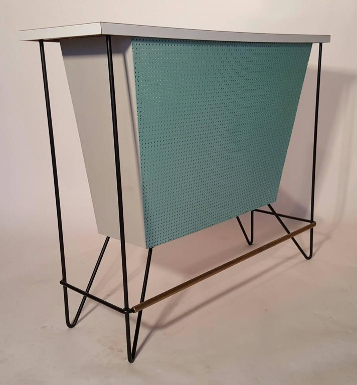 One of the lesser seen versions.. Classic Frederick Weinberg free-standing dry bar and two matching stools.. Bar retains all original finish.. white laminate top.. Perforated turquoise wood panel front, brass and iron.. Original wire iron bar