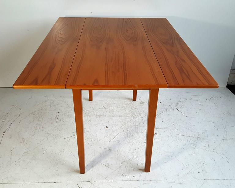 Classic Scandinavian design, sleek, simple, solid teak drop-leaf dining table, wonderful book matched graining, very versatile, when leaves are down table measures 47