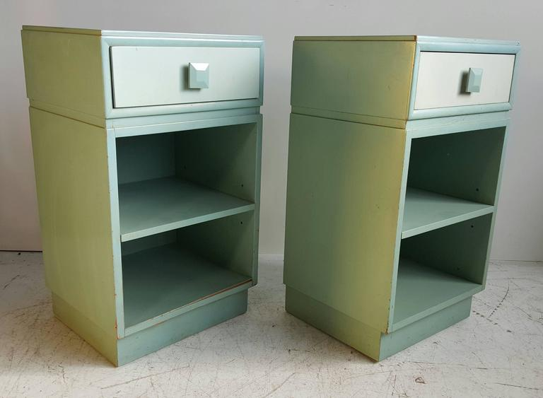 Great pair of 1940s side tables with drawer. The two-tone finish in original factory paint, visible wear. Shelf is adjustable. Drawer marked with Kittinger foil label.