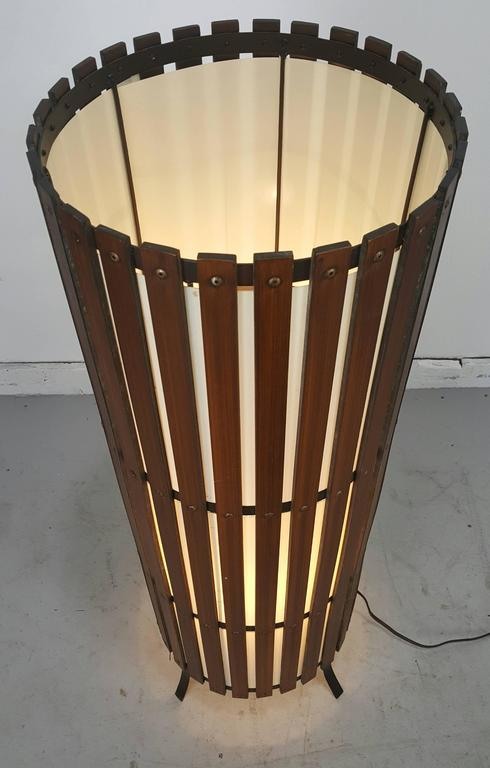 Contemporary modernist walnut slat wood cylinder floor lamp. Quality solid oiled walnut slats, retains original cylinder white acrylic shade, black metal fee. Wonderful warm glow when illuminated.