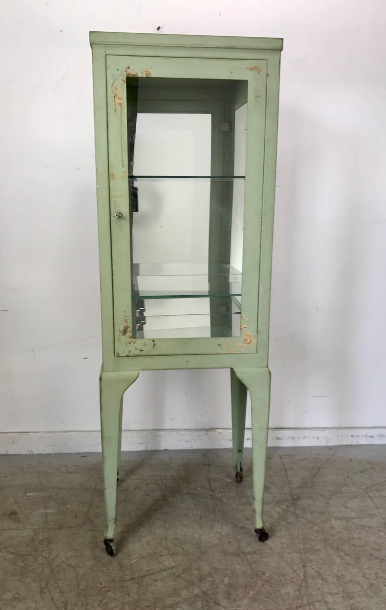 Classic 1920s metal and glass specimen cabinet, medical, Industrial. Wonderful patina color, surface and proportion, retains original locking mechanism and key, hand delivery avail to New York city or anywhere en route from Buffalo New York.