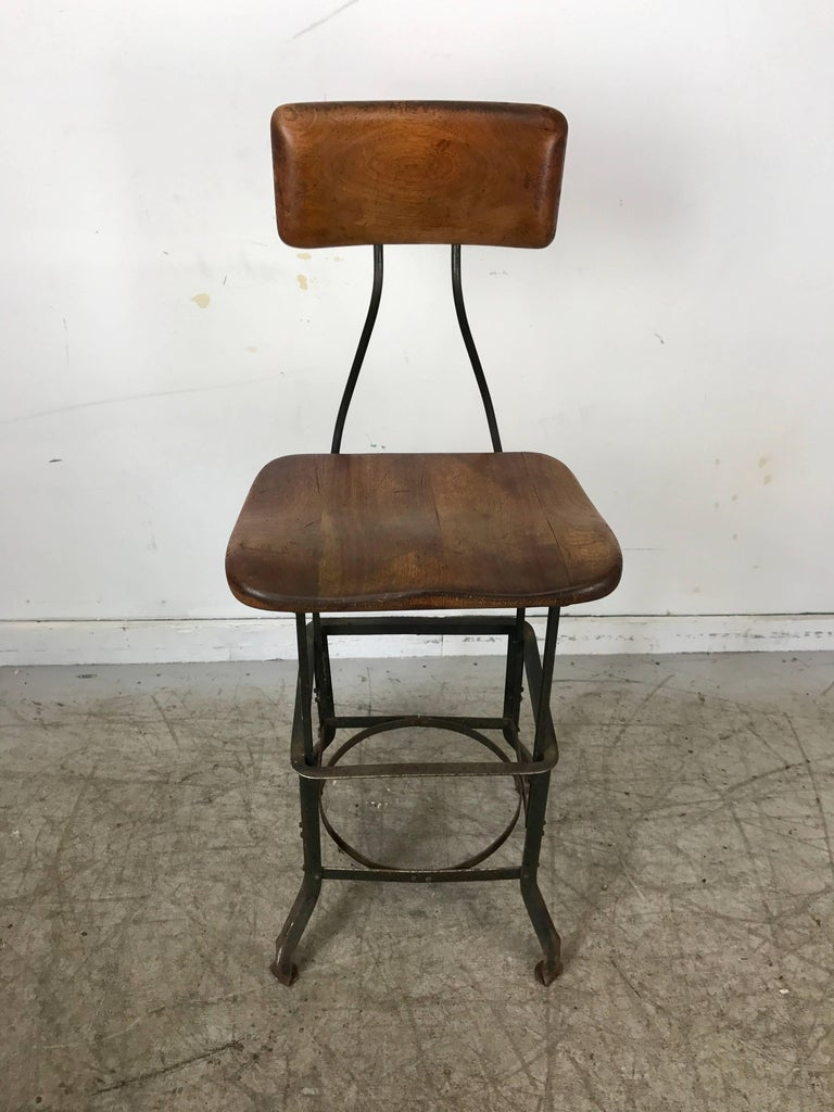 Early adjustable Industrial machinist stool, manufactured by Toledo,, Wonderful original patina color and surface. Solid carved wood top and back.
