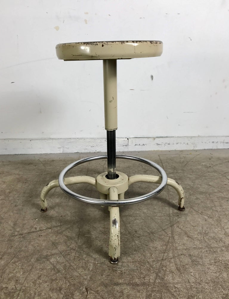 Set of four Industrial adjustable metal stools manufactured by Ajusto Equipment Co. Multi height position, ingenious design! Lift and drop to desired height, wonderful patina, 360 degree swivel. Measure from 17 inches to 24 inches H, seat measures