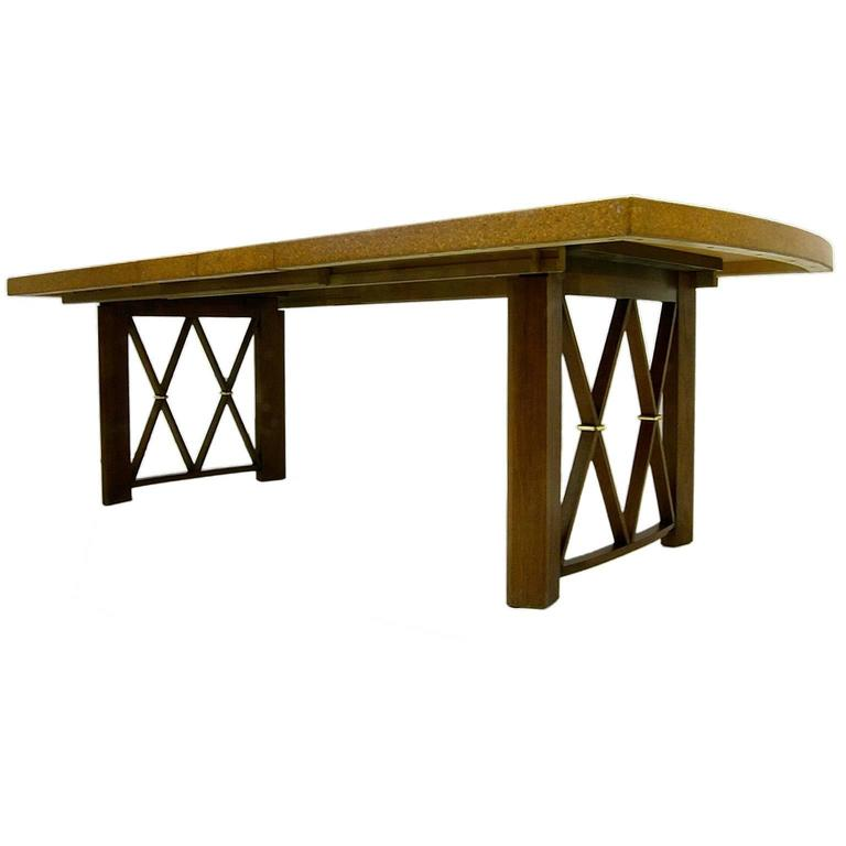 A stunning dining table with cork top and mahogany legs and X detail with brass accent. Designed by Paul Frankl for Johnson Furniture. Measurement includes two 12 inch leaves.