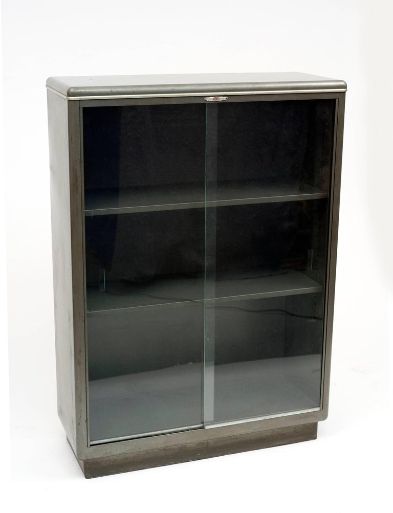 Fantastic 1940s, hard to find,  American streamlined Industrial bookcase. Bookcase is complete with original sliding glass doors on ball bearings. Everything is original including. Metal shelves are adjustable. Well designed bookcase is a great way