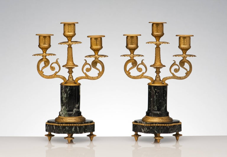 Finely made pair of candelabras from France, 1920s. Beautiful bronze detailing. Carved marble columns and base. Condition is excellent.