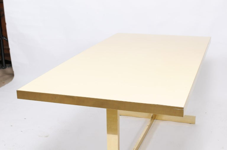 A vintage Italian dining table from the mid-20th century, with formica rectangular top and brass trestle base. This stately Mid-Century Modern Italian vintage table has some minor scratches from age on the formica, but we don't think it deters from
