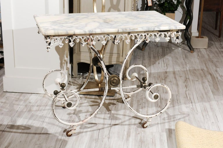 A French white painted iron baker's table on casters from the early 20th century with rectangular marble top, Gothic-inspired apron, scrolling base and brass medallions. The lovely marble top for this French 1920s pastry table is what caught our eye