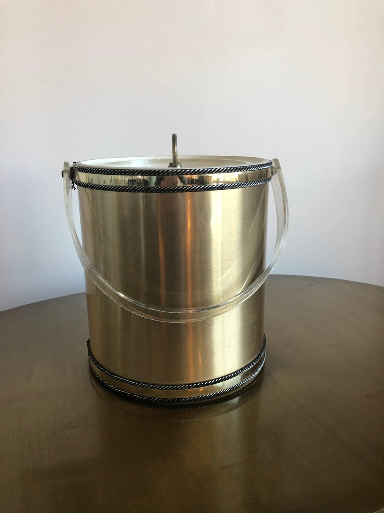 Offered is a signed Mid-Century Modern Georges Briard brushed brass and Lucite ice bucket. The brushed brass ice bucket has a cylindrical shape with bands of polished brass at the top and bottom bordered by applied roping with a clear Lucite swing