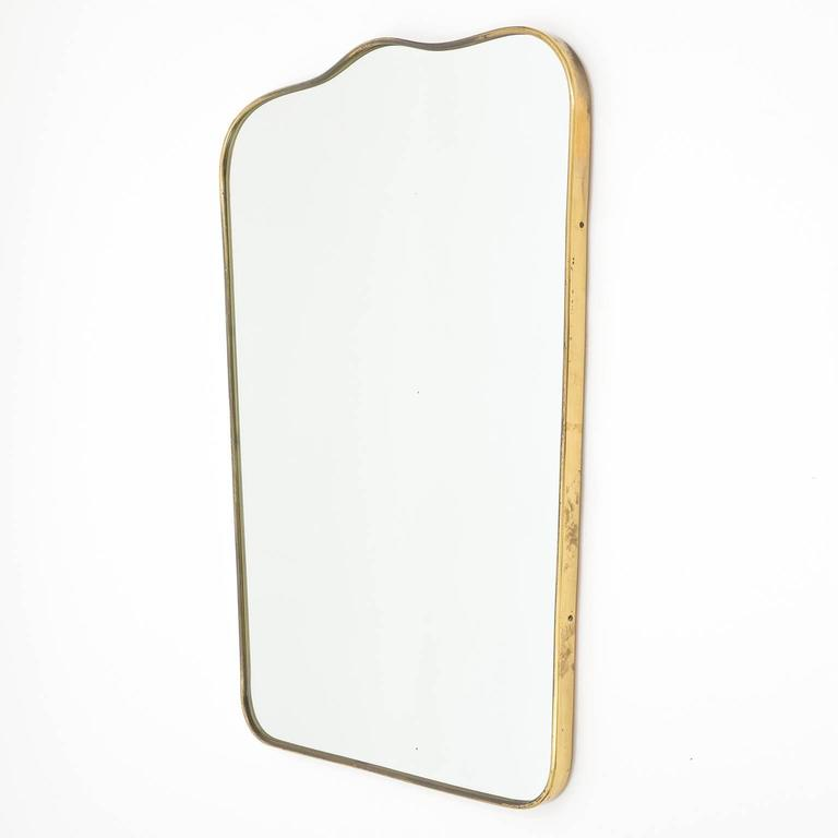 Elegant Gio Ponti style brass mirror from the 1950s. Has a nice patina on the brass and a few minor age-related specks in the mirror. Measuring width on the bottom is 18.5inches/47cm.