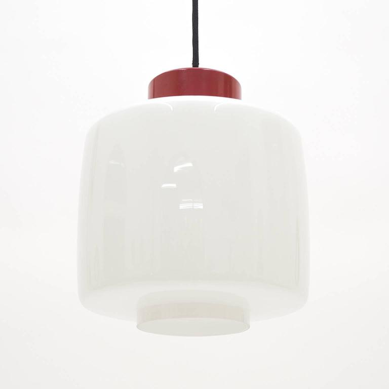 Classic modernist Stilnovo pendant from the 1950s. The blown glass has a total of four layers, alternating between clear and white casing, and a red lacquered 'cap' which houses the original E27 socket with new textile wiring. Drop height is