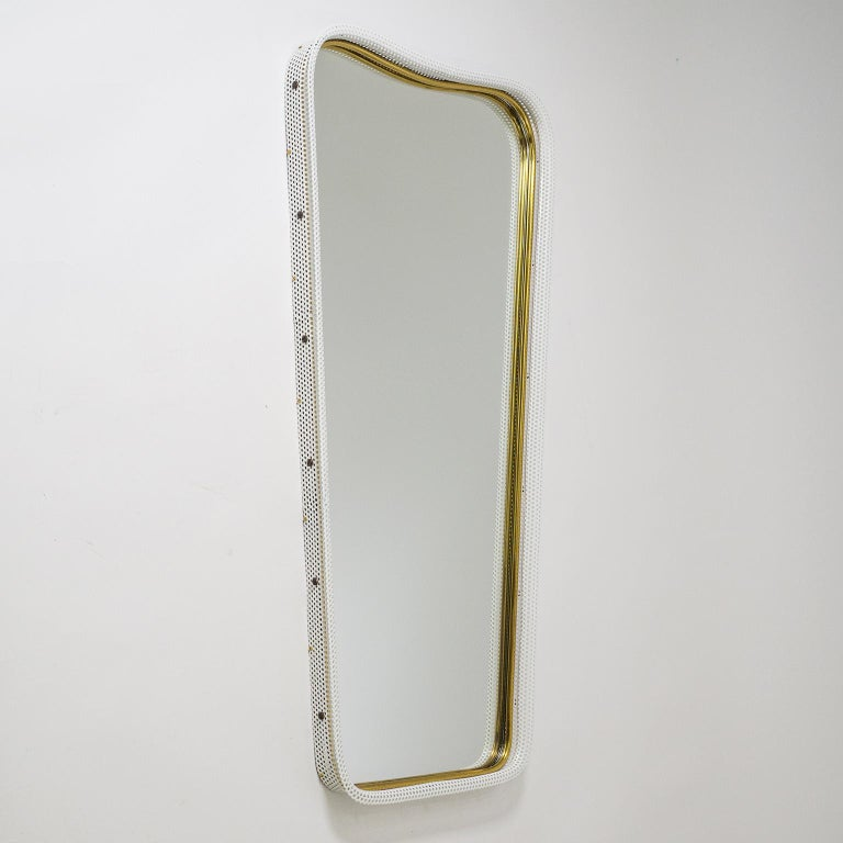 Very unique midcentury wall mirror with a sculpted perforated metal frame in white and a tubular brass inner rim. Excellent craftsmanship with original mirror in very good shape.