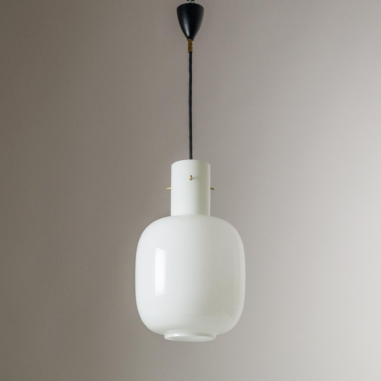 Modernist Italian glass pendant attributed to Stilnovo, 1950s. Nicely sized and proportioned glass body made of 'triplex opal' glass which is very typical of Stilnovo. The glass body is suspended by three brass stems. One original brass and ceramic