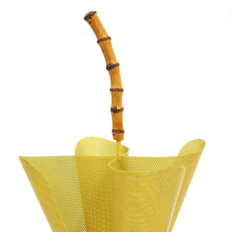 Gorgeous midcentury umbrella stand in the shape of an half-way open umbrella. A perky bamboo grip on top of mustard colored perforated metal with a brass base (including a solid steel weight for stability). Very nice original condition with just