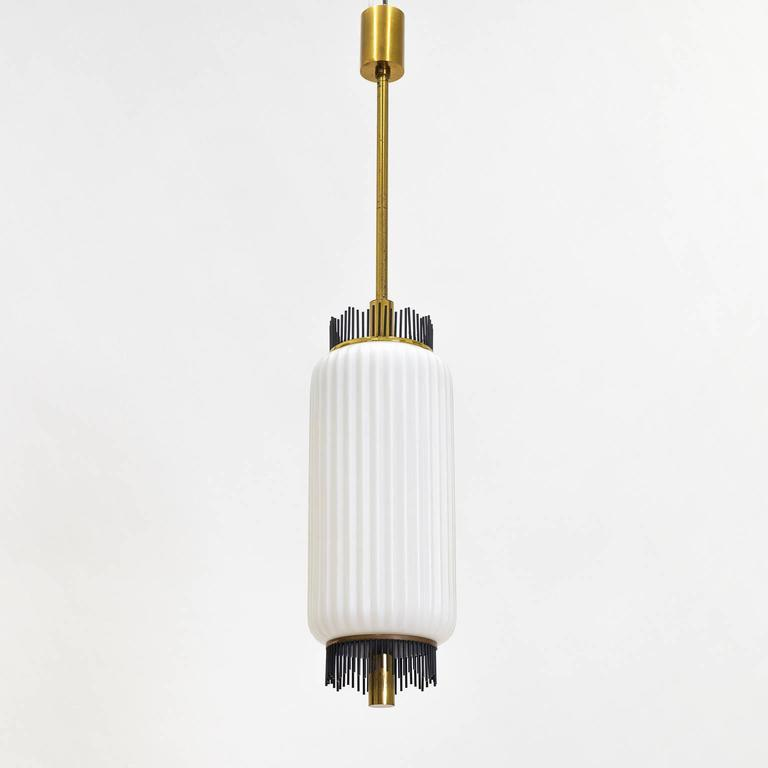 Superb modernist Arredoluce pendant with a graphical touch composed of a large ribbed glass body and brass hardware. The brass 'wires' and 'covers' on the top and bottom of the glass body are lacquered in black. Very good original condition with