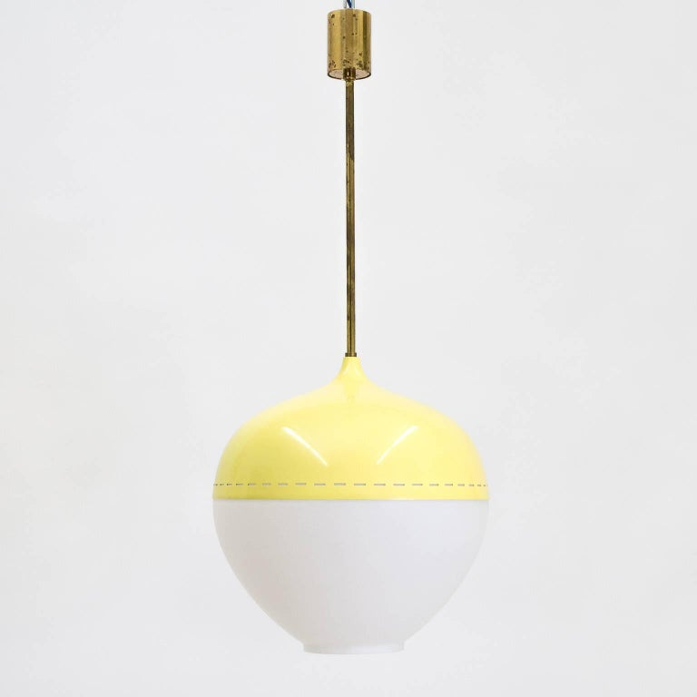 Rare Stilnovo pendant from the 1950s. A large onion shaped satin glass globe is partially covered by a pierced and lacquered aluminum shade and mounted on brass hardware. The shade has a pastel yellow color with linear piercings along the edge for a