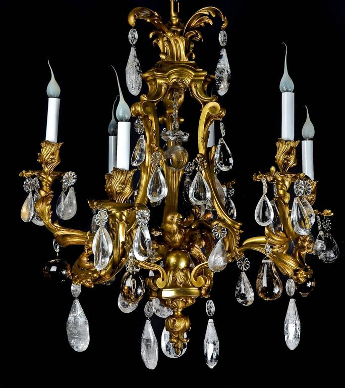 An antique French Louis XVI style gilt bronze and cut rock crystal multi light cage form chandelier of fine detail embellished with a central gilt bronze parrot and further embellished with fine rock crystal prisms.
