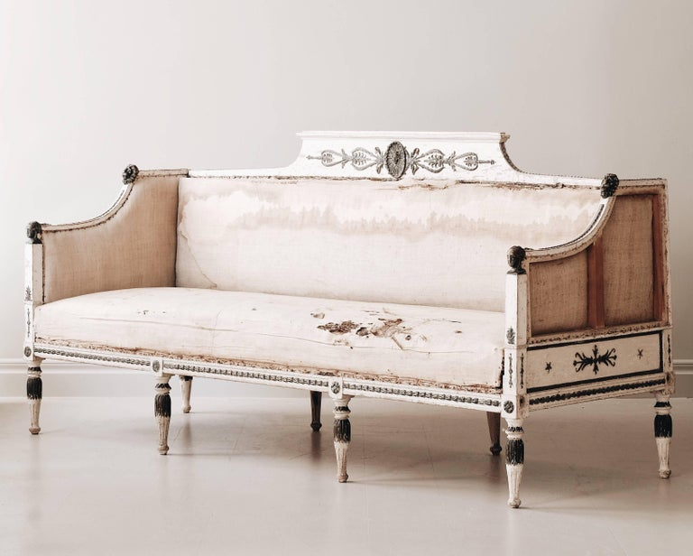 Fine 19th century late Gustavian sofa inspired by the Roman Empire and ancient Egypt. The sofa has its original padding left and is in original color with faux oxidized copper painted to the carvings, lion heads and female heads on the armrests.