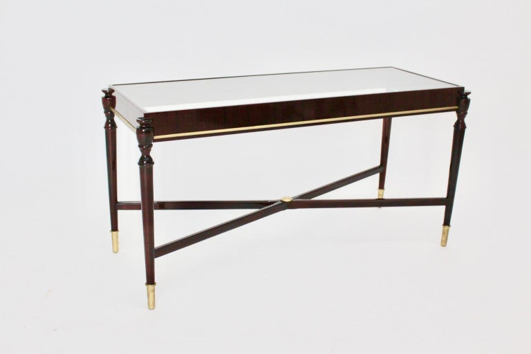 This side table was made of solid mahogany and veneered mahogany, lacquered. The side table features golden details and a clear glass top.  Very good condition  Measures: Width 108.5 cm Depth 44 cm Height 55.5 cm.