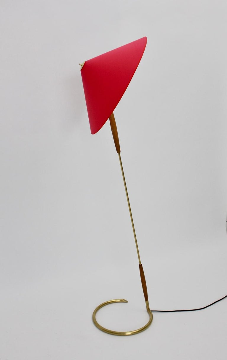 This elegant floor lamp by Guiseppe Ostuni attributed consists of a brass and beechwood stem and a renewed lamp shade covered with red textile fabric. An integrated on/off switch at the socket. One E 27 socket.  Measures: Diameter 56.5 cm Height 158