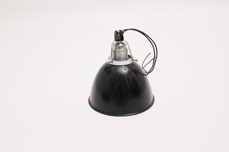 Simple black and white enameled Bauhaus hanging lamp, 1920s, Germany.  The hanging lamp consists of enameled metal, chromed metal and a porcelain E 27 socket.  Very good condition with signs of age. Measures: Diameter 18 cm Height 18 cm.