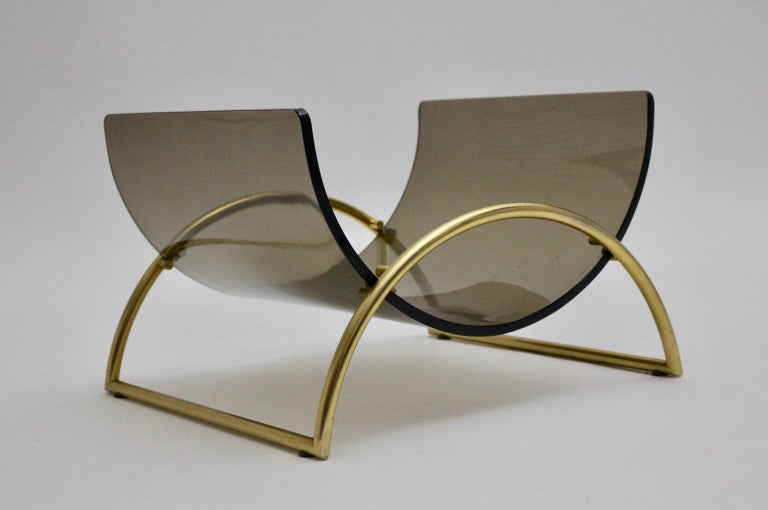 This presented magazine rack named Lira L1 was designed by Pierangelo Gallotti and manufactured by Gallotti & Radice, Italy. The elegant magazine rack features a gilded aluminium base and a smoked curved glass. The condition is very good with