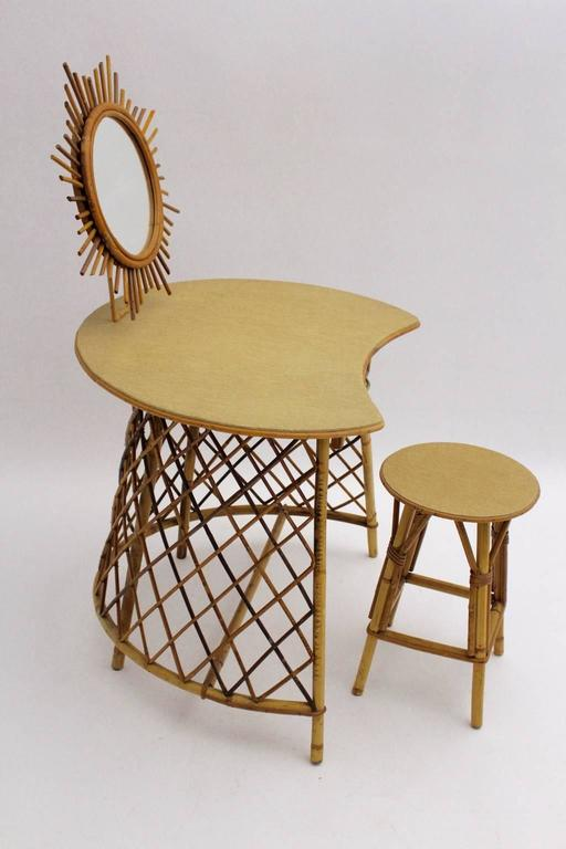 This presented charming vanity was made of rattan and features a matching stool. Furthermore the vanity is topped with a sunburst mirror.  Also the table has one drawer and the surface is covered with linen. The vanity is in best vintage