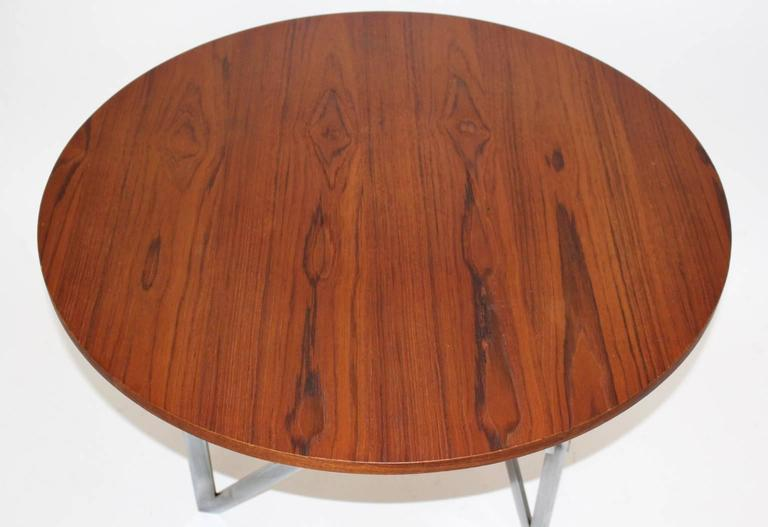 Three legged coffee table designed by Aksel Bender Madsen (1916-2000) & Ejner Larsen (1917-1987) in Denmark, circa 1960. The base is made of chromed steel furthermore the top was made of teak. Very good vintage condition. All measures are