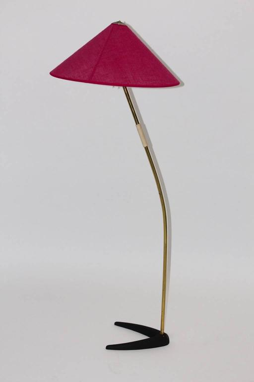 Wonderful floorlamp with brass curved stem and a black lacquered cast iron clawfoot.  Plastic white handle Designed by J. T. Kalmar in Vienna, Austria, 1950´s The portable shade is newly covered with raspberry fabric. It is possible to lift the