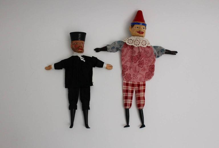 Art deco vintage glove puppetry, which consists of 10 different characters: Mr. Punch, King, Queen, Grandmother, Devil, Teacher, Policeman, Good Guy, Bandit, Oriental. The heads, feet and the hands were made of hand carved wood and are various