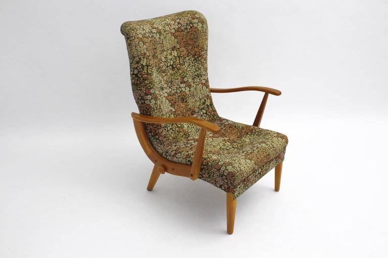 This lounge chair is made in Austria, 1950s. The frame is made of solid beechwood and decorated with one button on each side. The upholstery is covered with flower design textile fabric in warm colors. Seat height: 16.54 in (42 cm).  Carefully