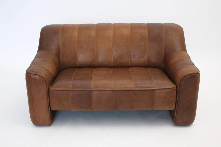 Fantastic De Sede leather sofa in the color cognac and extandable seat (3.94 in-10cm.)  Wood and metal frame covered with leather in the color cognac. Very good vintage condition with wonderful leather patina. The Loveseat shows no stains, just one
