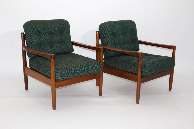 Beautiful sitting room set designed by Grete Jalk, circa 1955, consist of two armchairs and one coffee table, made of teakwood. The cushions are covered with the original textile woolen fabric, which shows a wonderful green-blue color. Carefully