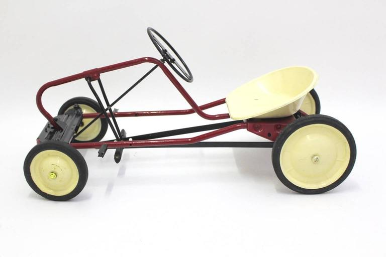 The pedal car was made of tube steel base partially black and red brown and ivory lacquered. The wheels and the pedals were made of rubber, furthermore the seat shell was made of plastic and shows no cracks. The original condition is very good. This