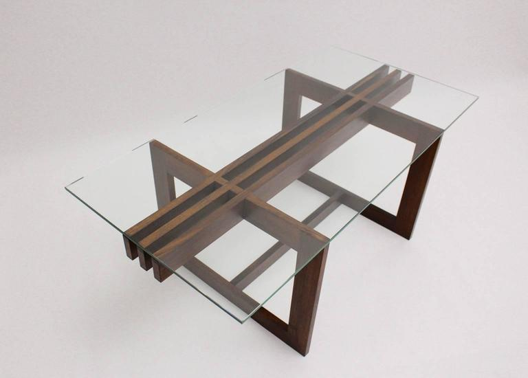 A Scandinavian Modern vintage teak coffee table, which shows a geometric base construction with a clear glass top ( thickness 0.39 in ). All measures are approximate.
