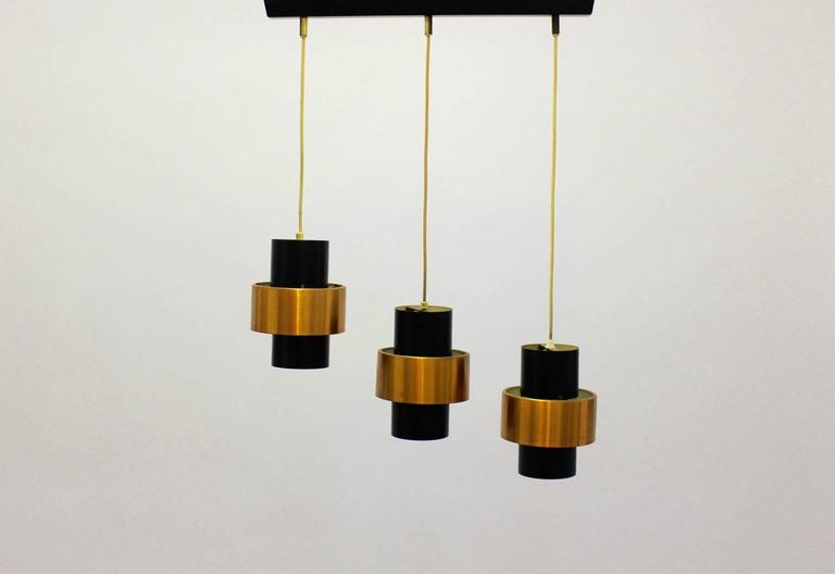 This chandelier features three shades shaped like tubes, which were made of copper and metal black lacquered. The shades are fixed with cords on the trail and there are three fittings for Edison 27. The item was designed by Jo Hammerborg and