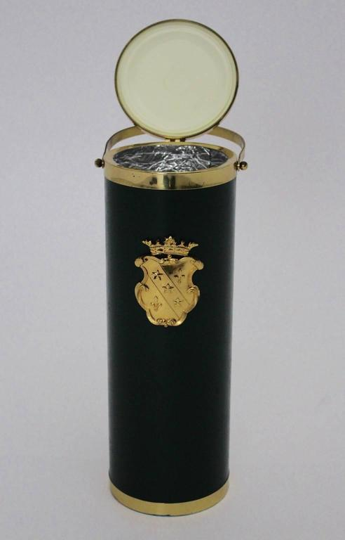 The wine cooler was made of a brass plated metal base and also made of waxed green faux leather. The front side is decorated with a golden crown.  The wine cooler was fitted with a silver foil covering.  The vintage condition of this wine cooler is