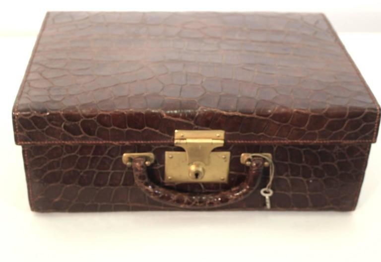 The art deco alligator traveling grooming leather case is lined with red leather and features various compartments replete with glass bottles with gold lids, leather boxes, flacons and a mirror. The leather case is lockable with the original key and