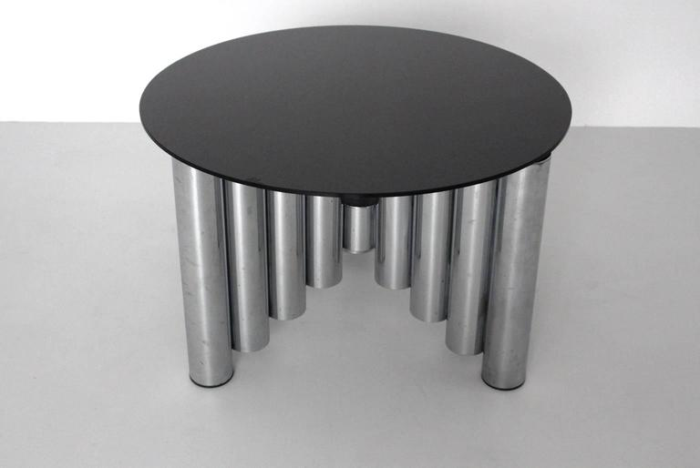 The coffee table has a chromed tube steel base and a black colored glass top with fine scratches.  The chromed tubes are shaped like the skyline of Manhattan. All measures are approximate.