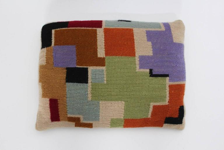 The original Art Deco Era pillow features a multicolored embroidery and comes with an insert. The both sides show different geometric pattern colored in black, green, lilac, light blue, brown, ivory, orange and red.  The original condition is good.