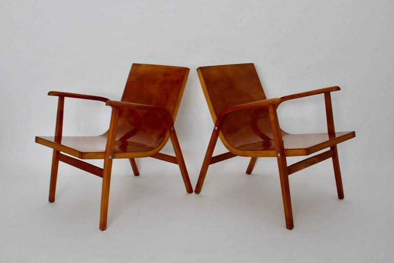 The pair of lounge chairs was designed by Roland Rainer, Vienna 1952 for the Cafe Ritter in Vienna, and manufactured by Emil & Alfred Pollak, Vienna.  The simple and chic lounge chairs are made of solid bent beechwood and plywood. The seat and the