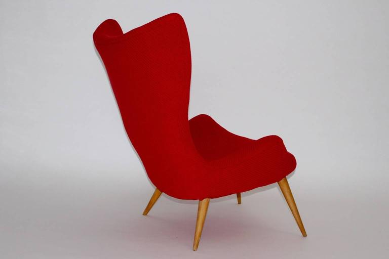 The red lounge chair from the Mid-Century era has four beechwood feet. Also the renewed upholstery is covered with a luxurious textile fabric. The cocktail chair is very comfortable and looks like a sunbeam.