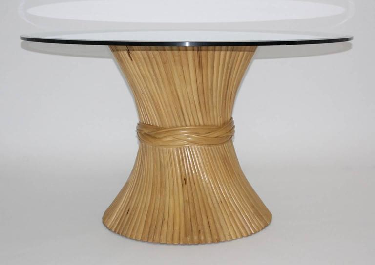A vintage bamboo dining table designed by McGuire, United States. The condition of the bamboo base is very good.   Measurements of the bamboo base: Diameter:  70 cm  Height: 74.5 cm   Measurements of the table with the glass top: Diameter 127.5