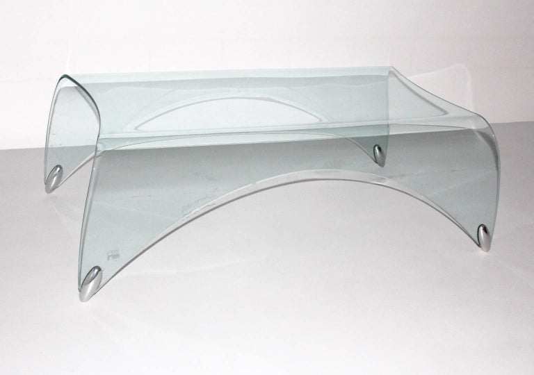 The glass coffee table by Massimo Iosa Ghini and executed by Fiamm, Italy has a great shape like a waterfall. The coffee table is made of safety glass.  During his simple and chic design this coffee table will match to every interior.  1986 Massimo